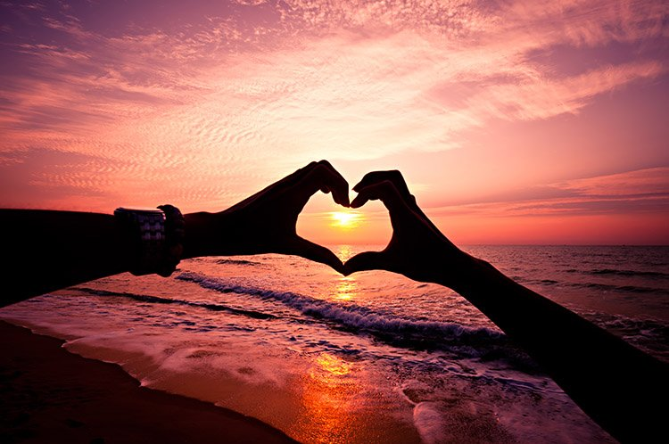 casal-fazendo-coracao-com-as-maos-em-frente-ao-por-d-sol-em-uma-praia